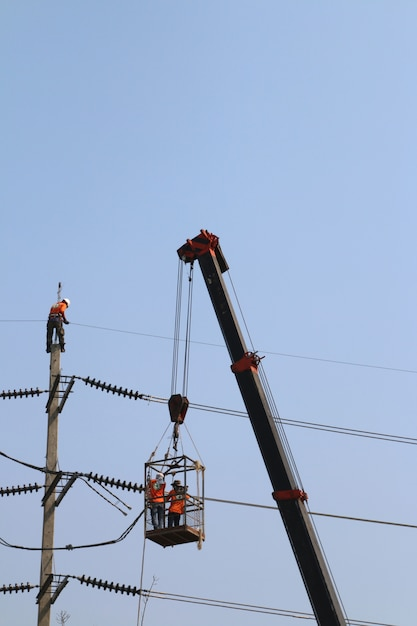 Elektricien die op hoogte werken door een hoogspanningsdraad aan te sluiten Premium Foto