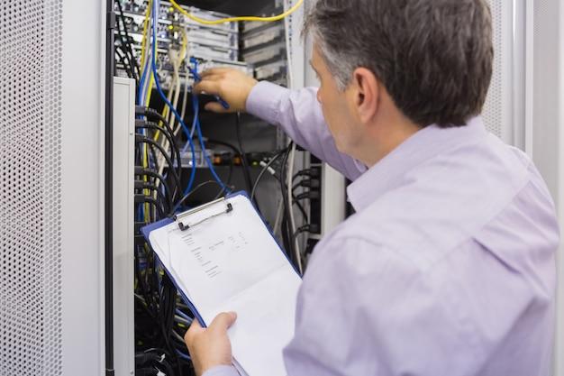 Elektricien die serveronderhoud met klembord doet Premium Foto