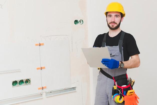 Elektricien die zich met document omslag bevindt Gratis Foto