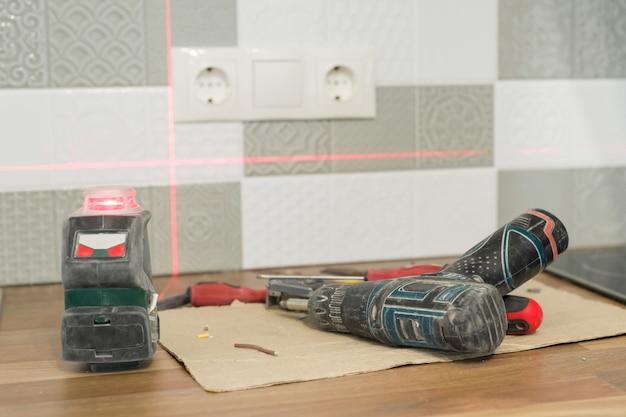 Elektricien met behulp van infrarood laserniveau om stopcontacten te installeren Premium Foto