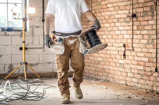 Elektricien met tools, werken op een bouwplaats. reparatie en klusjesman concept. Gratis Foto