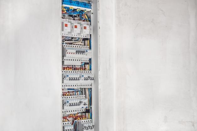 Elektricien, schakelbord met zekeringen. aansluiting en installatie in het elektrische paneel met moderne apparatuur. concept van complex werk. Gratis Foto