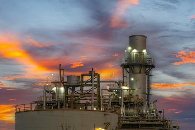Elektriciteitscentrale gas of olie voor de industrie bij schemering, energiecentrale met zonlicht Premium Foto