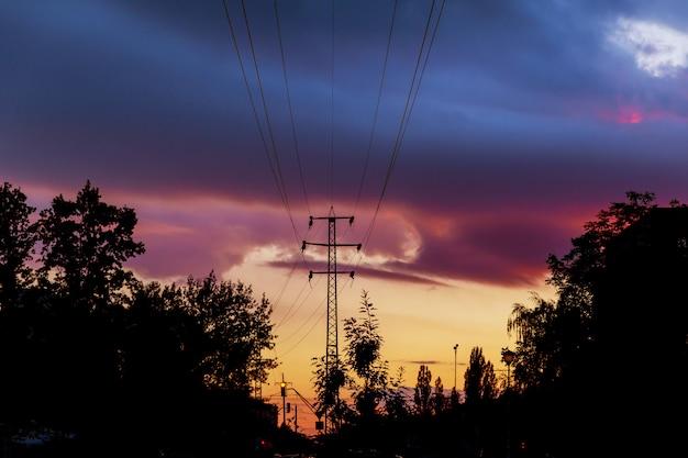 Elektriciteitslijnen afgetekend door hemel bij zonsondergang. Premium Foto