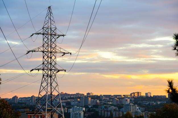 Elektriciteitspylonen en machtslijnensilhouetten bij een bewolkte zonsondergang. Premium Foto