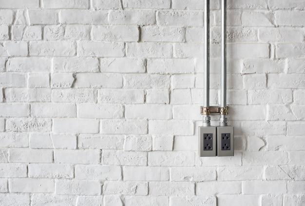 Elektrische aansluiting op een witte geschilderde bakstenen muur Gratis Foto