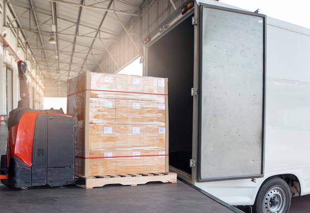 Elektrische heftruck palletkrik laden palletboxen in vrachtvrachtwagen. verzending, logistiek en transport Premium Foto