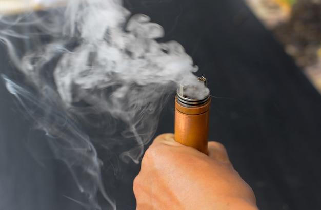 Elektrische sigaret in de hand branden met witte rook, e-sigaret, varpo. Premium Foto