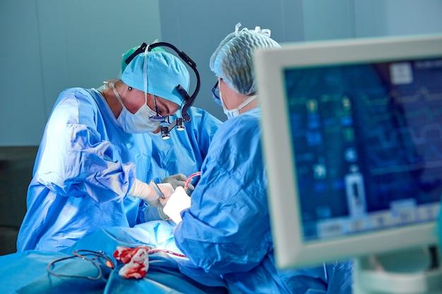 Elektrocardiogram in ziekenhuischirurgie die noodsituatieruimte toont die geduldige hartslag met onduidelijk beeldteam van chirurgenachtergrond toont Premium Foto