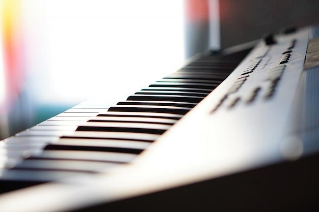Elektronisch synthesizer pianotoetsenbord in de stralenmacro van de zon. gekleurde stralen van lichte hi-tech. Premium Foto