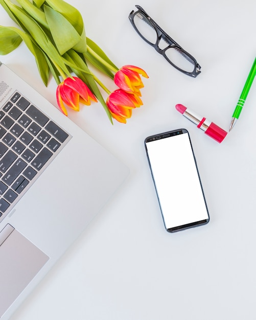 Elektronische apparaten in de buurt van bloemen, lippenstift en glazen Gratis Foto