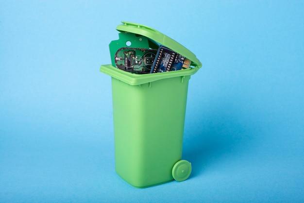 Elektronische componenten in een groene afvalmand Premium Foto