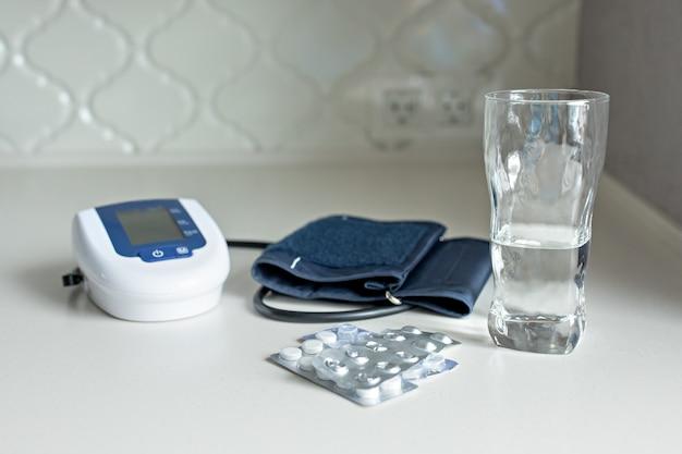 Elektronische tonometer, pillen en een glas water op een witte lijst Premium Foto