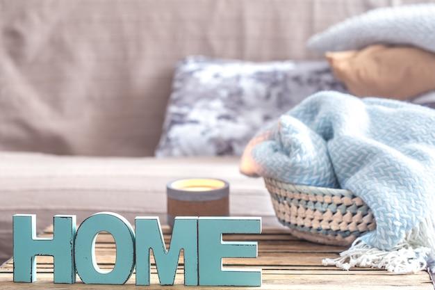 Elementen van gezellige huisinrichting op de tafel in de woonkamer met houten letters met het opschrift huis. Gratis Foto