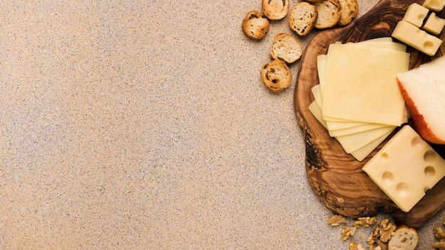Emmentaler en gouda kaas met plakjes op coaster met sneetjes brood en walnoot over beige gestructureerde achtergrond Gratis Foto