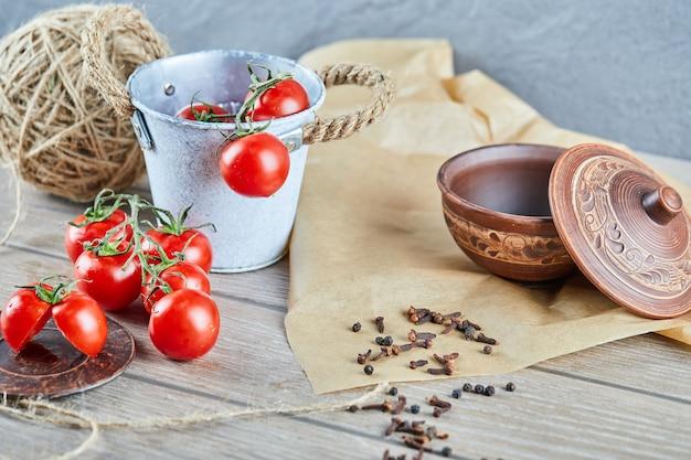 Emmer met tomaten en half gesneden tomaat op houten tafel met lege kom Gratis Foto