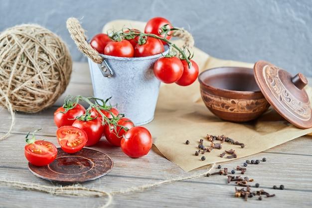 Emmer met tomaten en half gesneden tomaat op houten tafel Gratis Foto