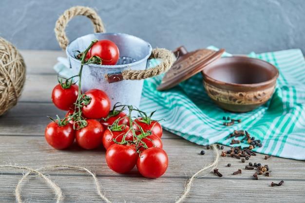 Emmer tomaten en kruidnagel op houten tafel met lege kom Gratis Foto