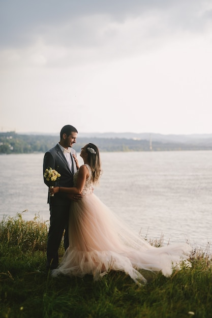 Emotioneel beeld van enkel echtpaar dat zich in gebied bevindt en elkaar met liefde bekijkt. rivier in de achtergrond. Premium Foto