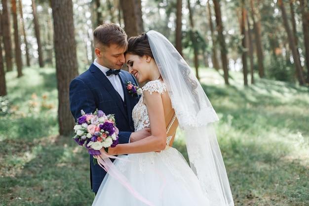 Emotioneel bruidspaar in het groene park in het voorjaar. lachende bruid en bruidegom in zonnige dag buitenshuis. gelukkige jonggehuwden knuffelen en zoenen op de trouwdag in de natuur. Premium Foto