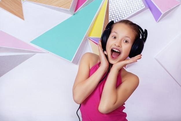 Emotioneel kindmeisje in hoofdtelefoons die aan muziek luisteren en zingen Premium Foto