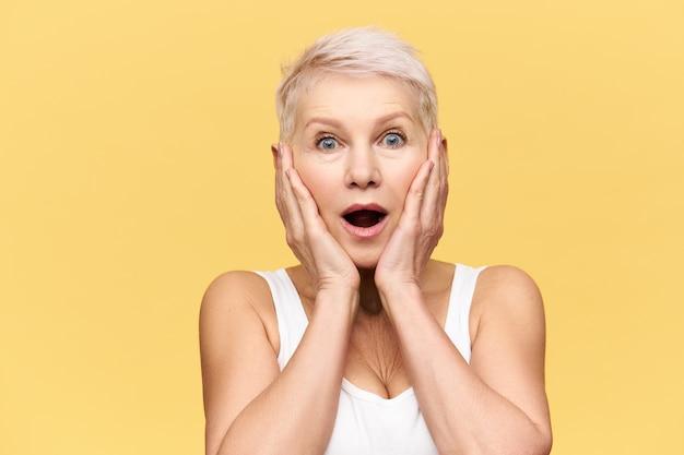 Emotioneel opgewonden blanke vrouw van middelbare leeftijd met blond pixiekapsel poseren geïsoleerd in wit tanktop hand in hand op haar gezicht, verbazing en vol ongeloof uitdrukken Gratis Foto