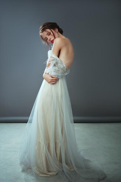 Emotioneel ouderwets portret van een vrouw in retrostijl in een licht transparante jurk met glanzende elementen op de schouders Premium Foto