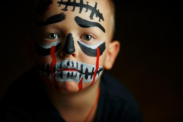 Emotioneel portret van een jongen met een enge zombie op zijn gezicht Premium Foto