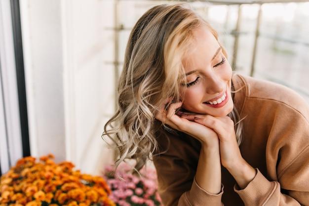 Emotioneel wit meisje dat met gesloten ogen glimlacht. portret van enthousiaste krullende vrouw zit in de buurt van oranje bloemen. Gratis Foto