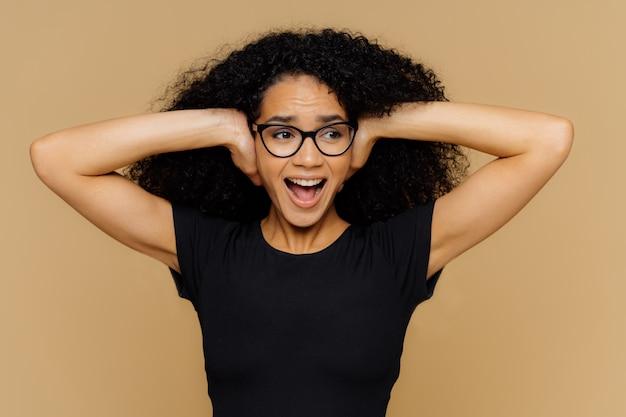 Emotionele afro-amerikaanse vrouw bedekt oren, schreeuwt luid, kan niet tegen lawaai en zet muziek uit Premium Foto