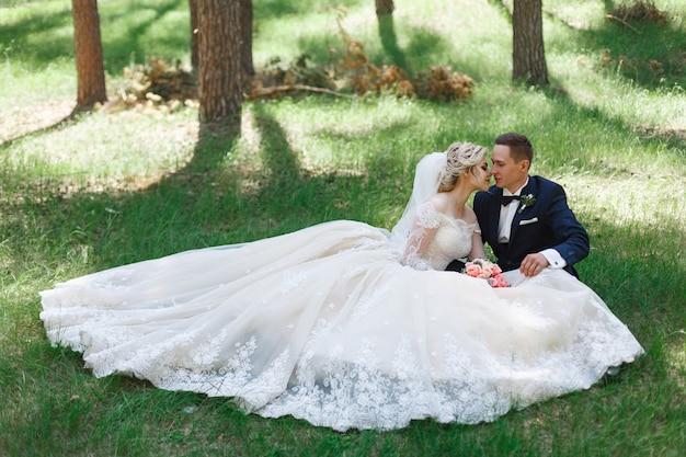 Emotionele bruidspaar op groen gras in het voorjaar. liefde van twee mensen. bruid en bruidegom zachte knuffelen en zoenen op trouwdag in de natuur. portret van prachtige pasgetrouwden buitenshuis. huwelijk concept Premium Foto
