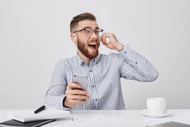 Emotionele dolgelukkig bebaarde man kijkt opgewonden opzij, luistert naar audiotrack met koptelefoon Gratis Foto