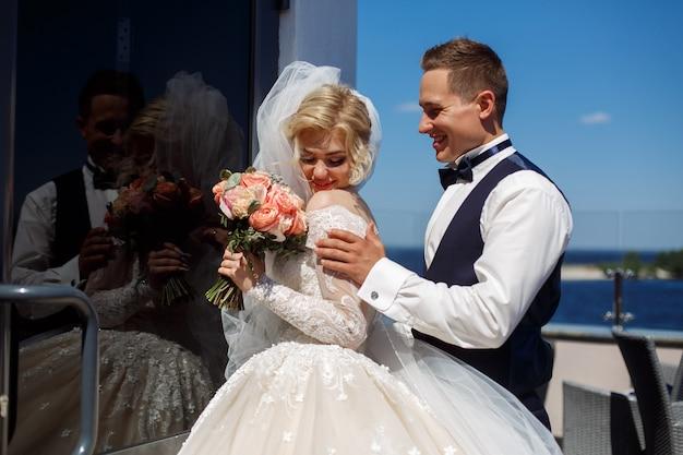 Emotionele foto van een verliefd paar op de trouwdag. lachende jonggehuwden. huwelijksfotografie. gelukkig net getrouwd stel Premium Foto