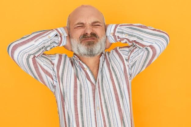 Emotionele gefrustreerde oudere europese man met kaal hoofd en grijze baard ogen sluiten en oren bedekken Gratis Foto