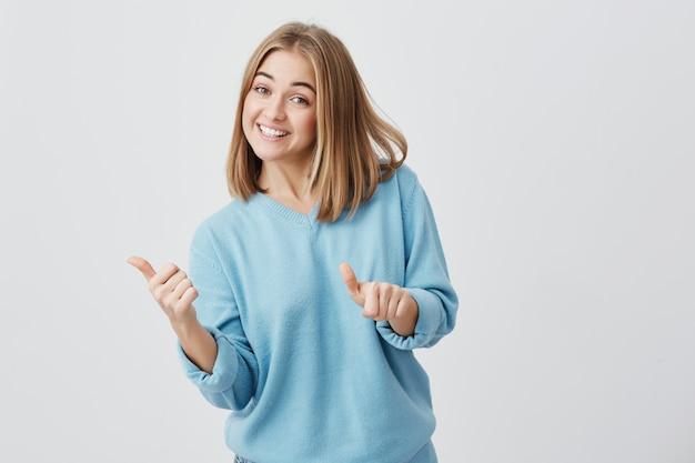 Emotionele gelukkig jonge blanke vrouw met blond haar gekleed in blauwe kleren geven haar duimen omhoog, waaruit blijkt hoe goed een product is. mooi meisje dat brodly met tanden glimlacht. gebaren en lichaamstaal Gratis Foto