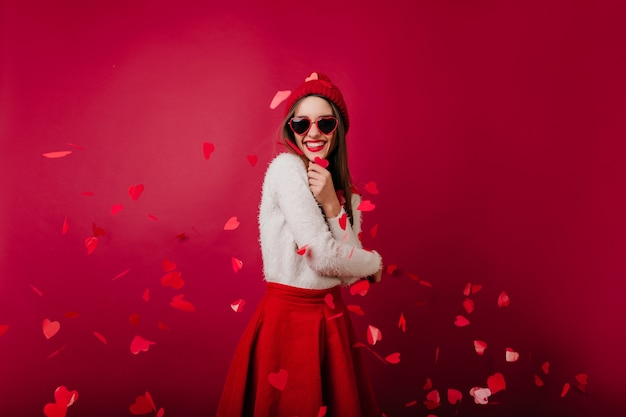 Emotionele jonge vrouw in rode hoed en zonnebril staande op bordeaux ruimte op feestje Gratis Foto