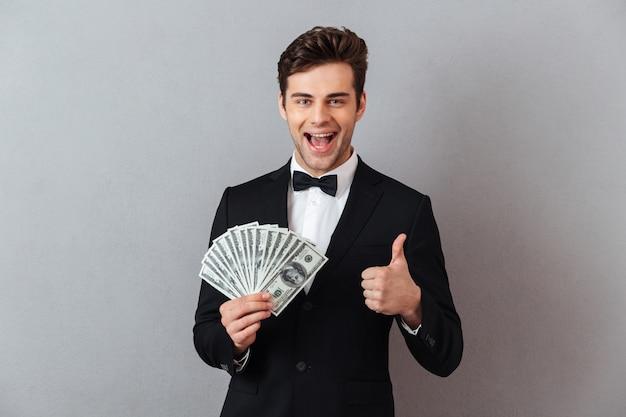 Emotionele man in officiële pak bedrijf geld zien thumbs up. Gratis Foto