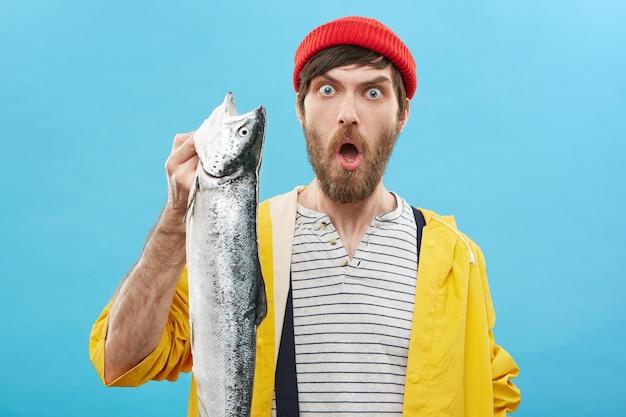 Emotionele man met rode hoed en gele regenjas met enorme lange zeevis in zijn hand Gratis Foto
