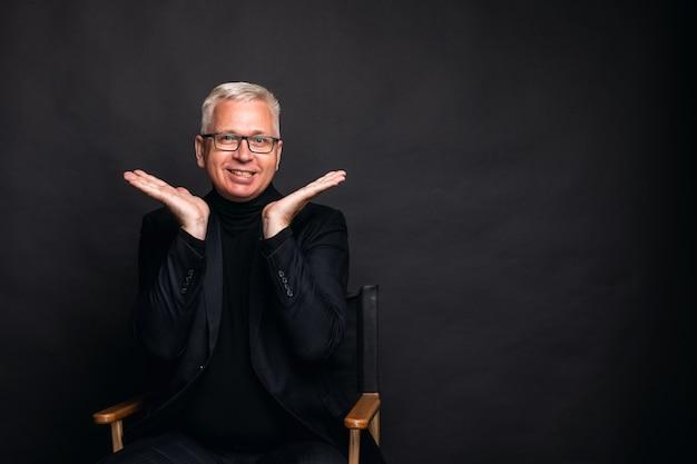 Emotionele man van middelbare leeftijd haalt zijn schouders op. een man van middelbare leeftijd met wit haar spreidt zijn handen rond zijn gezicht in een emotioneel gebaar. Premium Foto