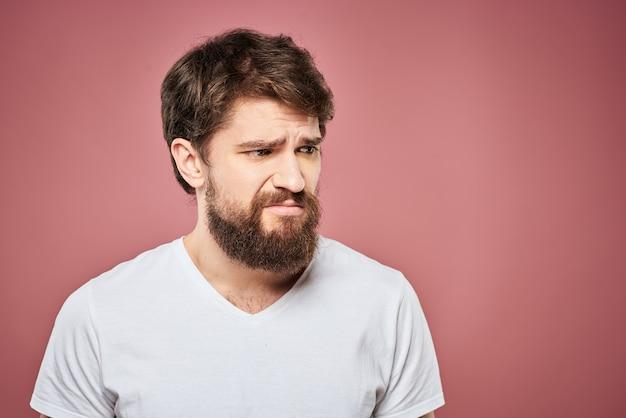Emotionele man witte t-shirt trieste gezichtsuitdrukking roze. Premium Foto