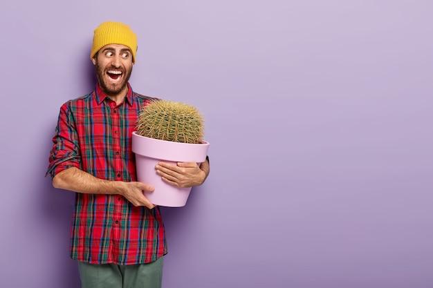 Emotionele mannelijke bloemist opent mond wijd, houdt pot met stekelige cactus, draagt gele hoed en geruit overhemd, poseert tegen paarse achtergrond, houdt van kamerplanten kweken, erg emotioneel Gratis Foto