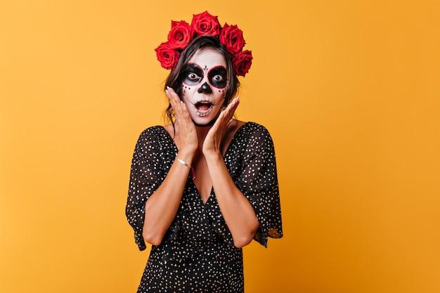 Emotionele mexicaanse donkerharige vrouw met bloemen op haar hoofd maakt geschokt gezicht zichzelf aan te raken met haar handen Gratis Foto