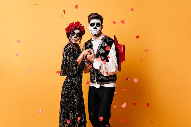 Emotionele paar hand in hand, poseren voor portret omringd door hartconfetti. elegante kostuums van jongens en meisjes vormen een aanvulling op hun ongebruikelijke imago voor halloween Gratis Foto