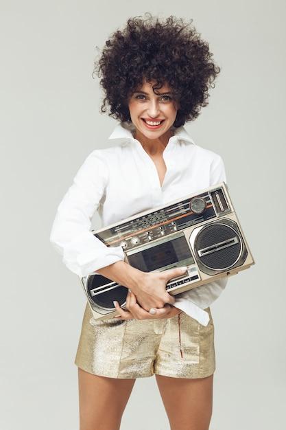 Emotionele retro vrouw gekleed in overhemd die boombox houden. Gratis Foto