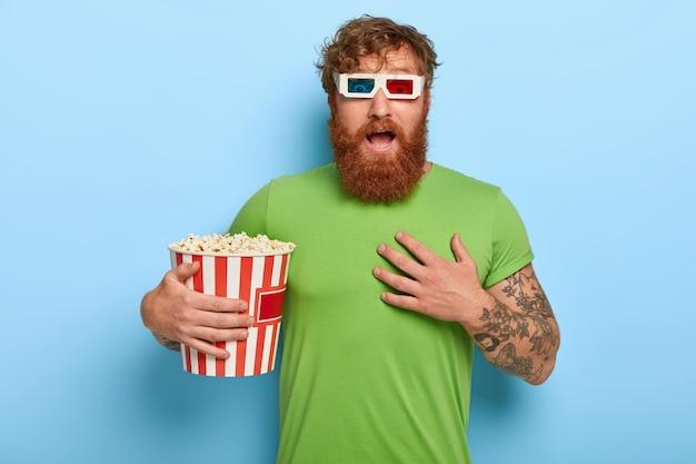 Emotionele roodharige man kijkt met grote schrik, kijkt horrorfilm alleen in de bioscoop, heeft ingehouden adem Gratis Foto