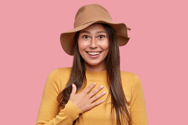 Emotionele verrast sproeterig vrouw met positieve uitdrukking houdt de hand op de borst, glimlacht breed naar de camera Gratis Foto