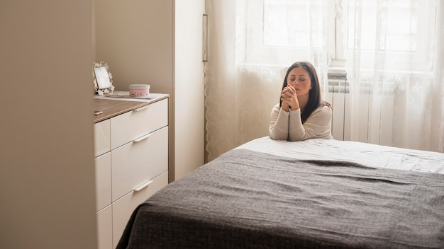 Emotionele vrouw die een gebed thuis zegt Gratis Foto