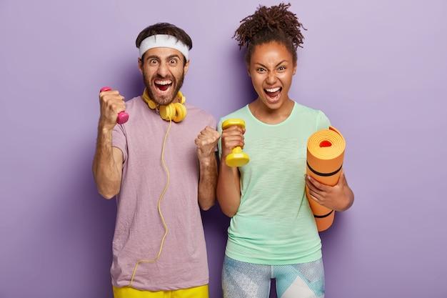 Emotionele vrouw en man van gemengd ras schreeuwen luid, houden karemat en gewichten vast, trainen met coach, schreeuwen van wanhoop, moe van training, geïsoleerd op paarse muur. mensen, sport, levensstijl Gratis Foto