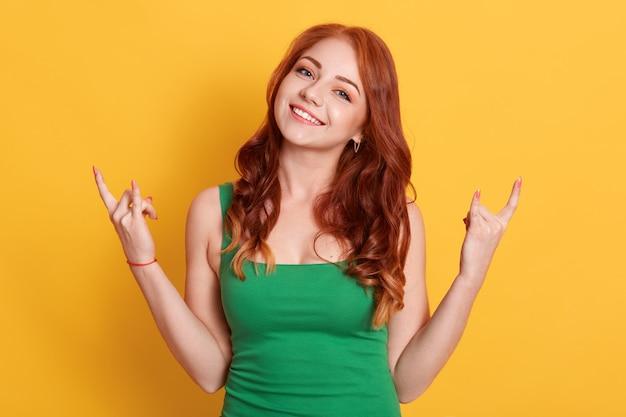 Emotionele vrouw maakt rock n roll-gebaar, geniet van coole muziek op feestje, toont handgebaar, gekleed groene outfit, modellen op gele achtergrond. Premium Foto