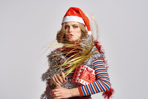Emotionele vrouw met takken van een feestelijke boom en rood klatergoud glb op haar hoofd gestreept zweet Premium Foto